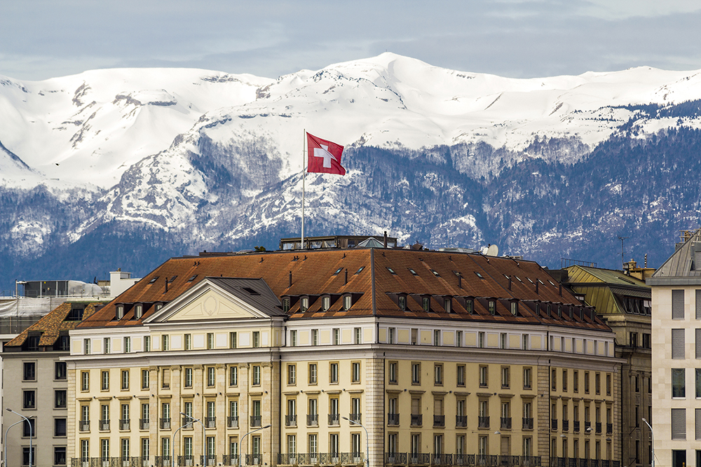Facades of historic buildings in the city center of geneva, switzerland on the leman lake with snow covered alps mountains peaks in sunny clear day